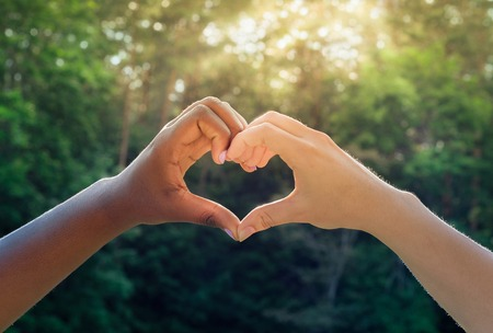 Black and white hands in heart shape, interracial friendship Stock Photo