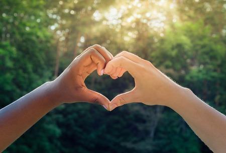 racismo: manos en blanco y negro en forma de corazón, amistad interracial