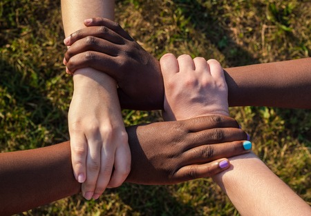 Hands of multiracial friends holding each other as team, cooperation concept