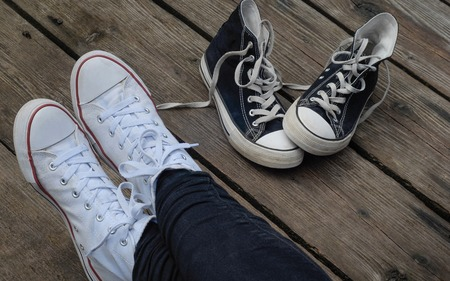 snickers: Teenager wearing white shoes sitting next to black snickers on the wooden bridge, choice concept