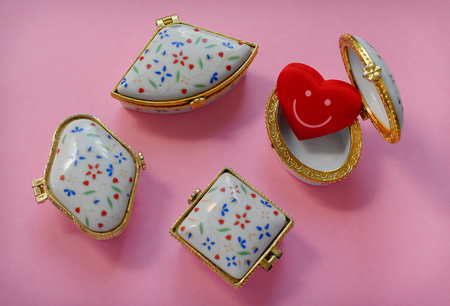 Jewelry boxes with one having a red smiley heart inside on pink background, top view Stock Photo