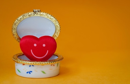 Jewelry box with a red smiley heart inside on yellow background
