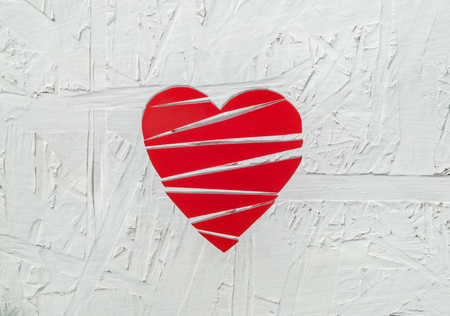 Paper broken heart on white wooden background
