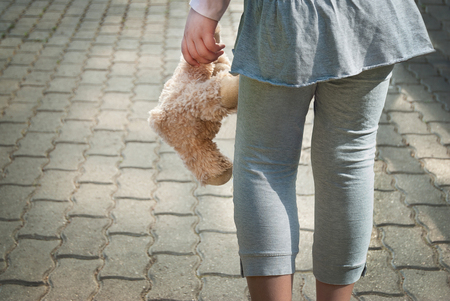 Lonely girl holding a teddy bear as her best friend Stock Photo