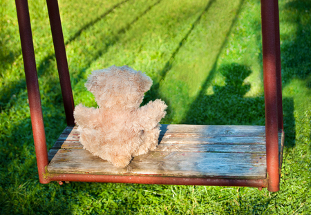 Teddy bear sitting on the swing. Loneliness concept.