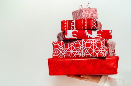 christmas spending: Womans hand holding a pile of nicely packed christmas gifts on white background Stock Photo