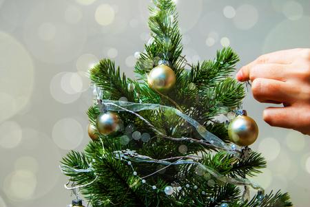 Woman hand decorating christmas tree with shiny ball, holidays concept.