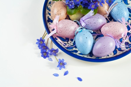 Colored eggs with violets on white background. Easter, Spring holidays