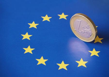 Closeup of a 1 euro coin on top of the European flag