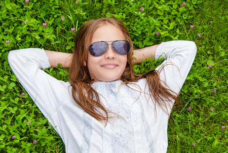 Young girl with sunglasses is relaxing on green grass, spring summer concept Stockfoto