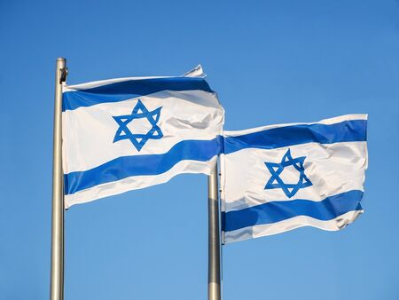 Two national flags of Israel outdoors against the blue sky