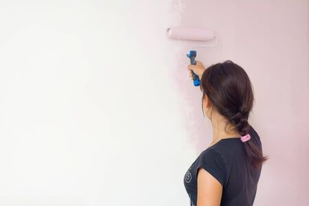 House repair, woman painting wall with a pink color Standard-Bild