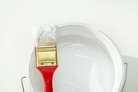 Painting equipment, paintbrush with a bucket of white paint on white background