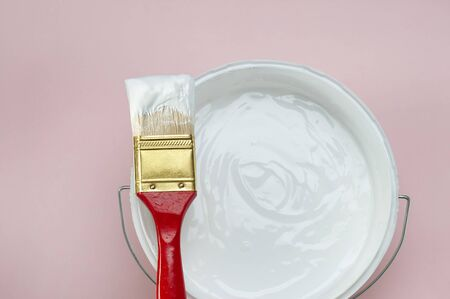 Painting equipment, paintbrush with a bucket of white paint on pink background