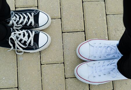 Teenagers with white and black sneakers, top view