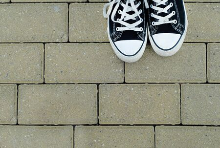 Teenager with black sneakers on the paving background, top view Фото со стока