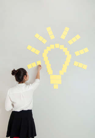 Idea concept, woman with yellow sticky notes shaped in light bulb
