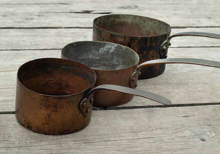Antique rusty copper pots on wooden background