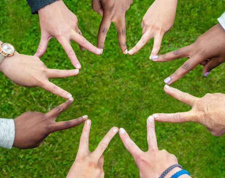 Black and white people forming nine pointed star with their fingers. 免版税图像