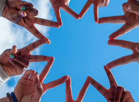 Black and white people forming nine pointed star with their fingers. Фото со стока