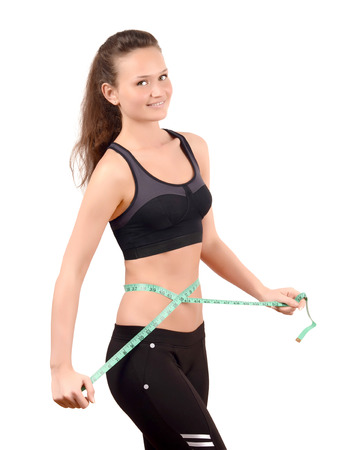 skinny woman: Beautiful fit girl measuring her waist with a green measuring tape in inch. Isolated on white. Stock Photo