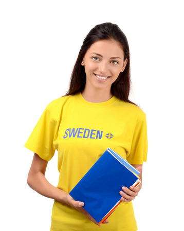 education in sweden: Learn Sweden. Beautiful student with Sweden flag on the yellow blouse holding books, blank blue cover book. Isolated on white.
