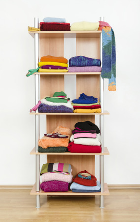 Winter clothes nicely arranged on a shelf  Tidy wardrobe with colorful clothes and accessories  photo