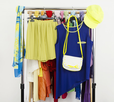 Cute neon green and blue outfit displayed on a rack. Wardrobe with colorful summer clothes and accessories