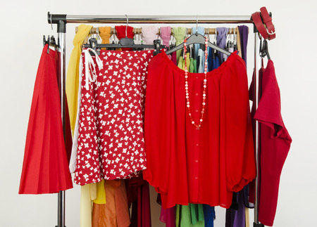 Cute summer red outfits displayed on a rack. Wardrobe with colorful summer clothes and accessories  photo