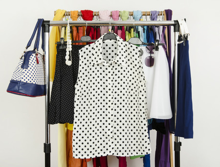Cute polka dots summer outfits displayed on a rack. Wardrobe with colorful summer clothes and accessories