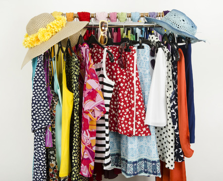 Cute summer outfits and wicker hats on a rack. Wardrobe with colorful summer clothes and accessories  photo