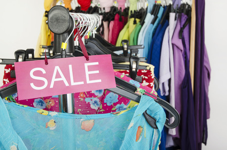 Close up on a big sale sign for summer clothes.  Clearance rack with colorful summer outfits and accessories displayed on hangers