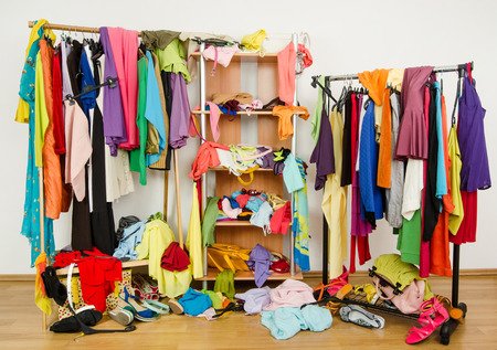 messy clothes: Untidy cluttered woman wardrobe with colorful clothes and accessories.  Messy clothes thrown on a shelf, on the ground and off the hangers and racks  Stock Photo