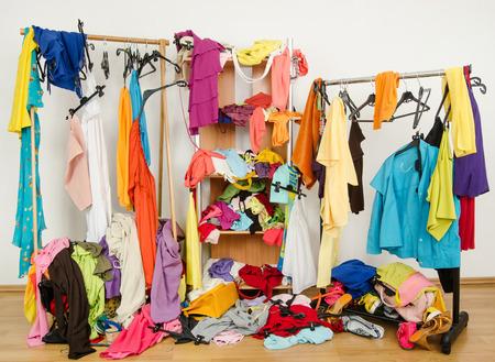 cuarto desordenado: Desordenado armario lleno de ropa de mujer de colores y accesorios. Ropa sucia arrojados en un estante, en la planta y fuera de las perchas y bastidores Foto de archivo