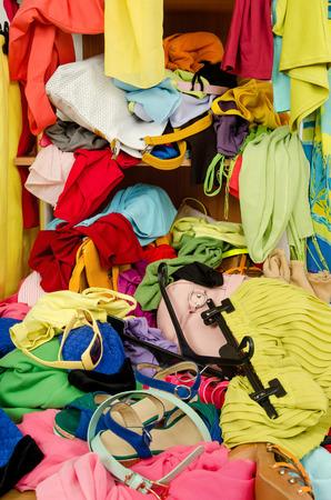 habitacion desordenada: Cerca de un gran mont�n de ropa y accesorios tirados en el suelo. Armario desordenado desordenado con ropa de colores y accesorios que caen de un estante Foto de archivo