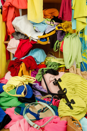 messy clothes: Close up on a big pile of clothes and accessories thrown on the ground.  Untidy cluttered wardrobe with colorful clothes and accessories falling out of a shelf