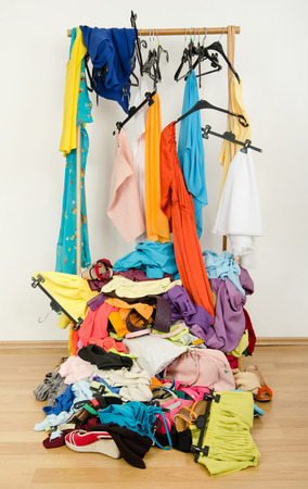 Untidy cluttered woman wardrobe with colorful clothes and accessories. Messy rack of clothes and hangers with a big pile thrown on the ground   photo