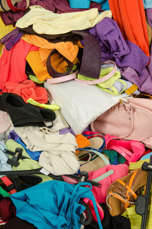 Close up on a big pile of clothes and accessories thrown on the ground. Untidy cluttered wardrobe with colorful clothes and accessories