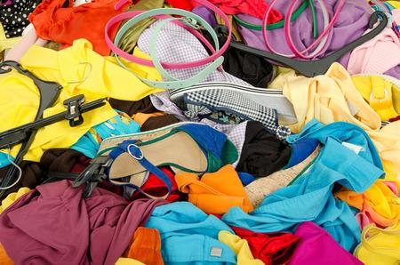 cuarto desordenado: Cerca de un gran montón de ropa y accesorios tirados en el suelo. Armario desordenado desordenado con ropas coloridas y accesorios Foto de archivo