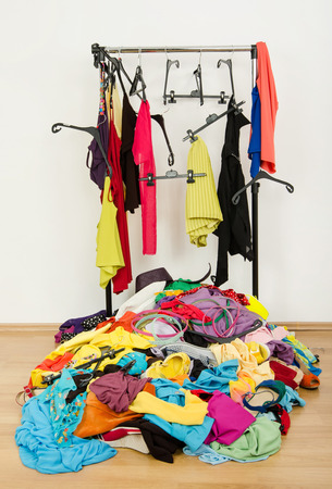messy clothes: Untidy cluttered woman wardrobe with colorful clothes and accessories. Messy rack of clothes and hangers with a big pile thrown on the ground  Stock Photo