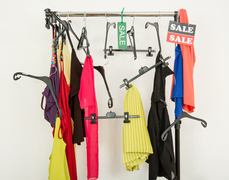 Messy rack of clothes and hangers after a big sale.  Sale sign for summer clothes on a clearance rack with colorful summer outfits and accessories  photo