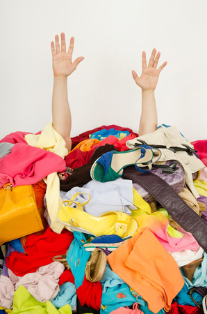 Man hands reaching out from a big pile of clothes and accessories. Man buried under an untidy cluttered woman wardrobe.  Man reaching for help from to much woman shopping  Stock Photo