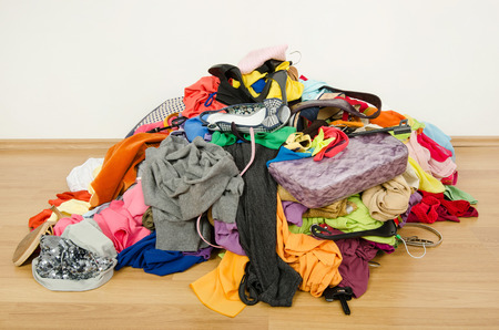 messy clothes: Big pile of clothes and accessories thrown on the ground.  Untidy cluttered woman wardrobe all on the floor  Stock Photo