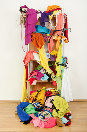 Untidy cluttered woman wardrobe with clothes and accessories falling out of a shelf Messy shelf with clothes and a big pile thrown on the ground
