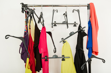 messy clothes: Messy rack of clothes and hangers  Untidy wardrobe with colorful summer outfits and accessories