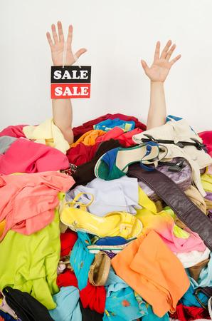 ropa de verano: Las manos del hombre con la muestra de la venta llegando de una gran pila de ropa y complementos