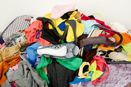 Close up on a big pile of clothes and accessories thrown on the ground  Untidy cluttered wardrobe with colorful clothes and accessories  photo
