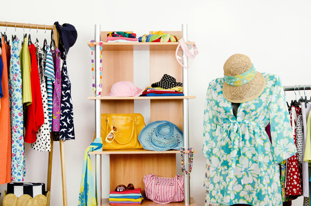 Wardrobe with summer clothes nicely arranged and a beach outfit on a mannequin Dressing closet with colorful clothes and accessories on hangers and a shelf