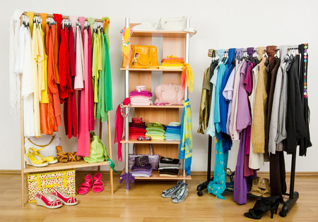Wardrobe with summer clothes nicely arranged  Dressing closet with color coordinated clothes and accessories on hangers and a shelf