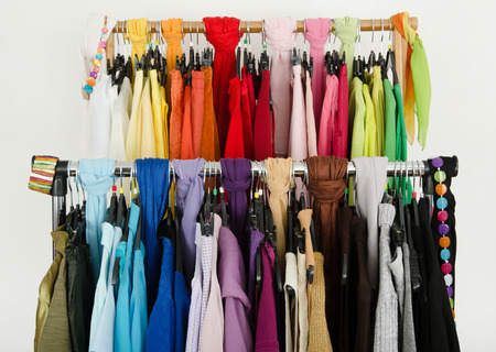 Close up on color coordinated clothes on hangers in a store All colors clothes hanging on a rack nicely arranged